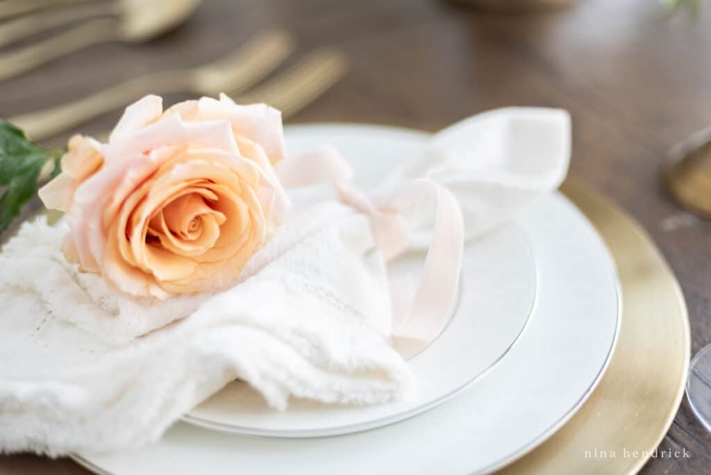 Place setting with blush rose and white frayed linen napkin, white plates, and a gold charger.