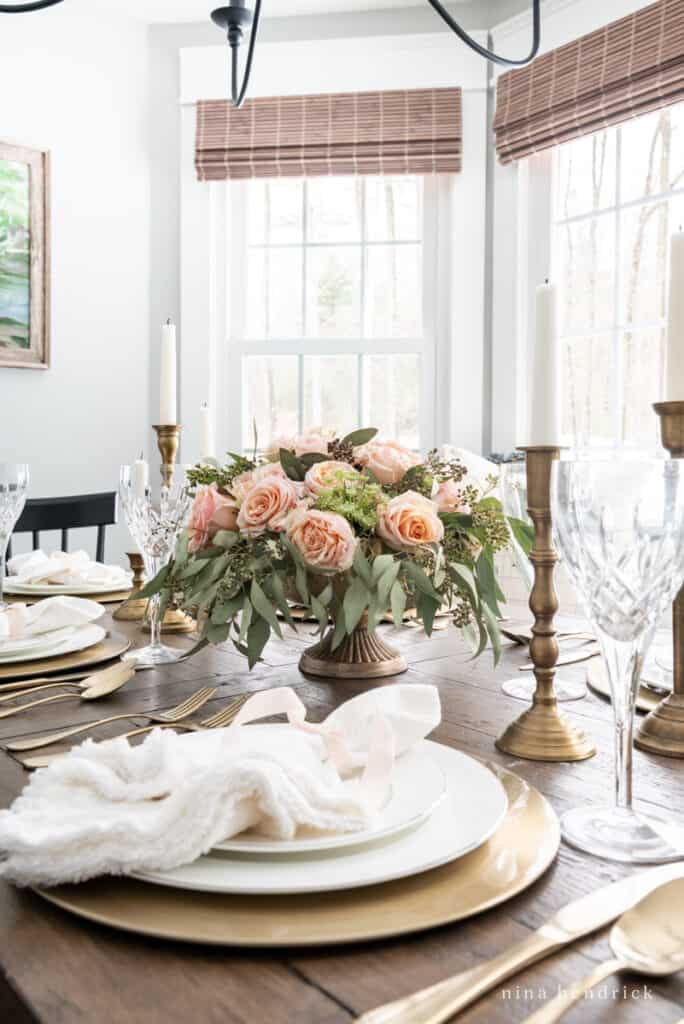 Blush Valentine's Day tablescape with gold chargers, candlesticks, and flatware.