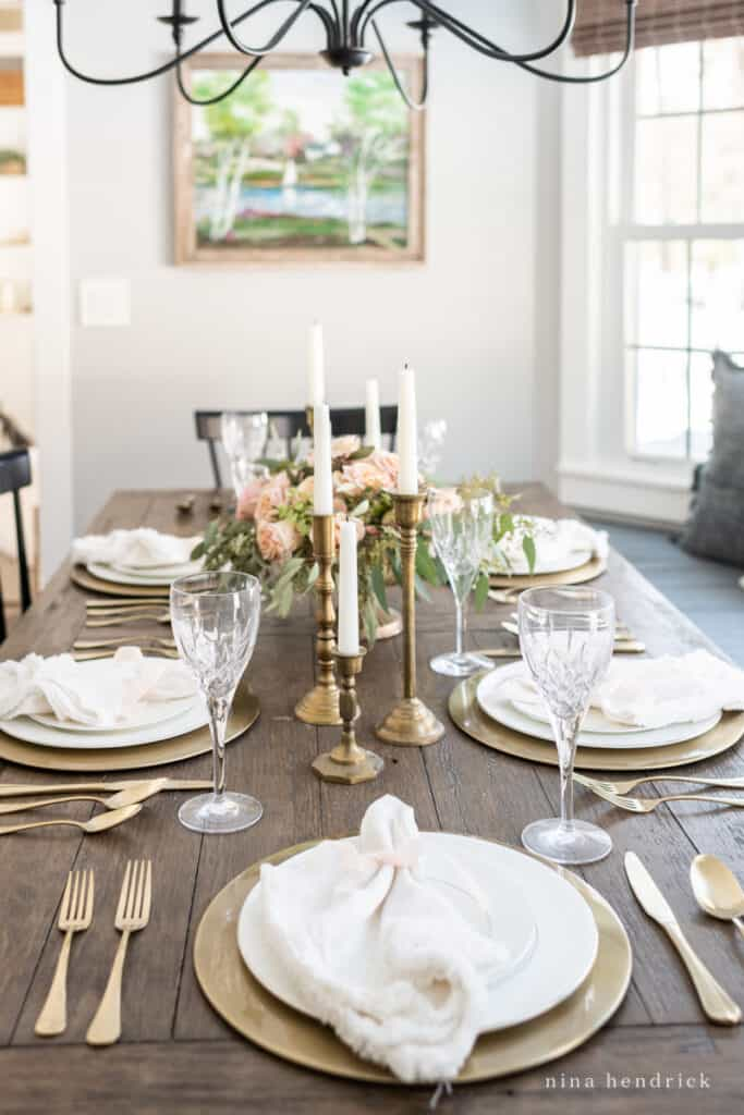 Gold place setting with white plates and a linen napkin with blush ribbon.