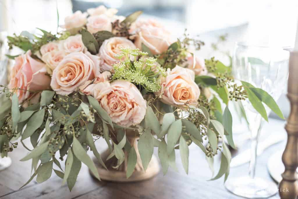 Floral arrangement with blush roses, seeded eucalyptus, and Queen Anne's Lace