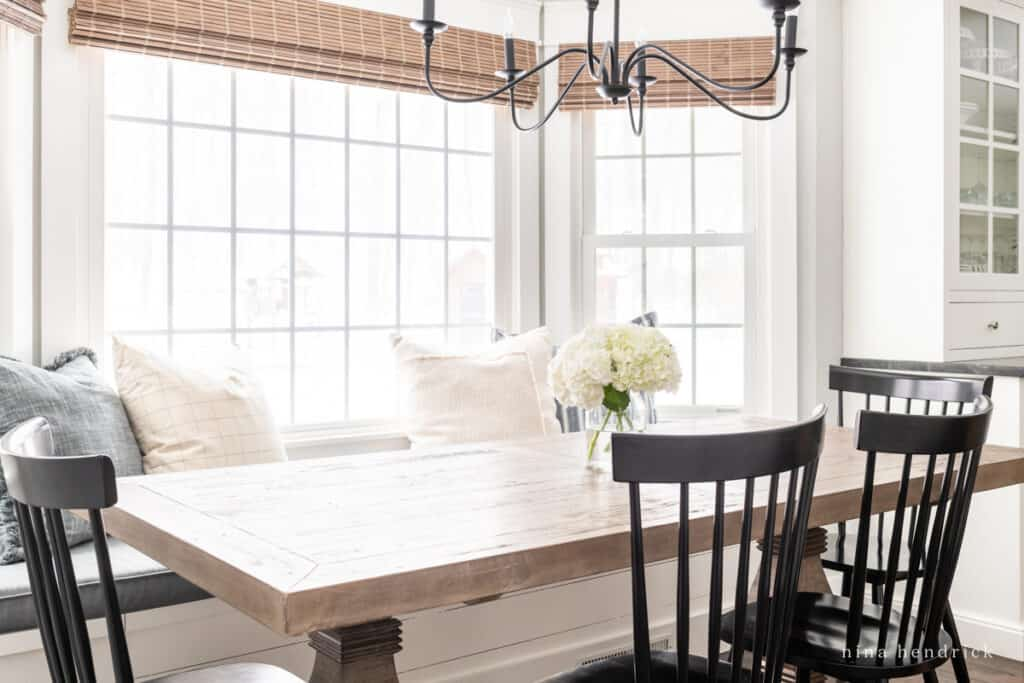 Breakfast Nook Refresh with black chairs and light fixture with woven shade and wood table