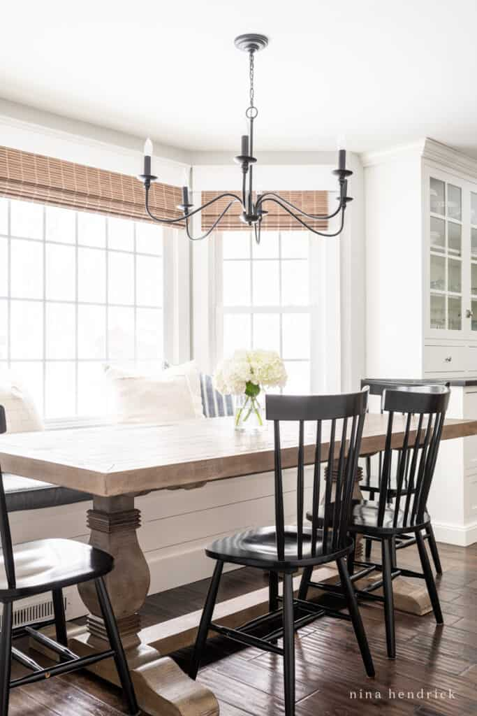 Dining area with bench and black Windsor chairs with iron chandelier and wood table
