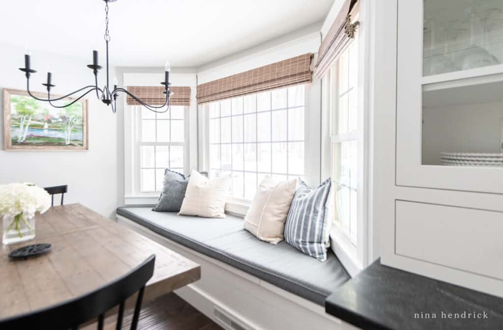 Bay window bench with cushion and soft neutral pillows