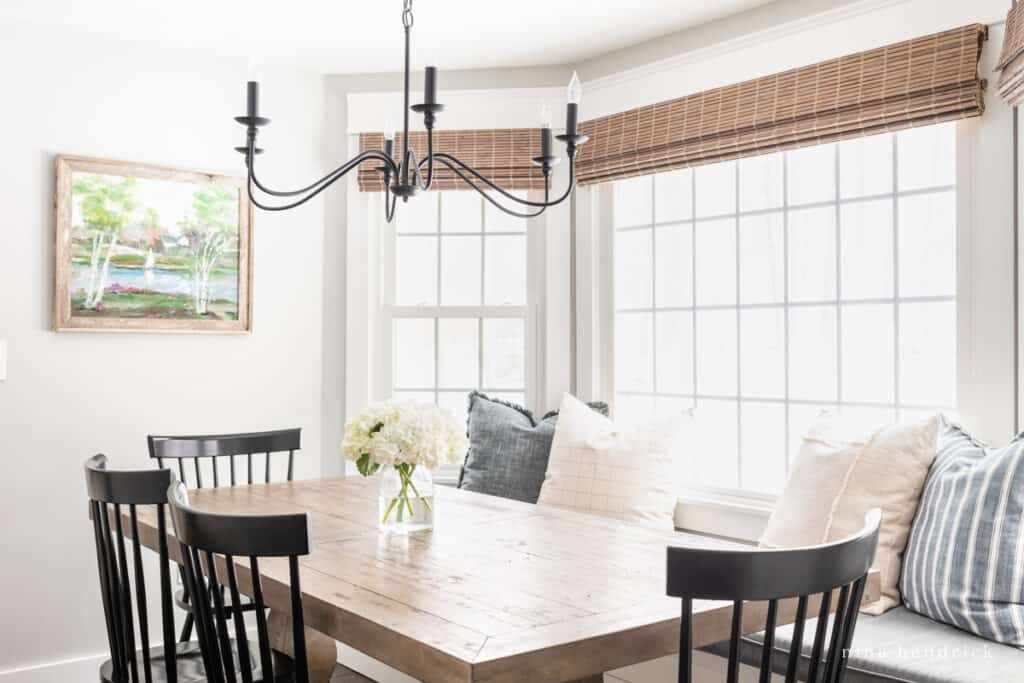 Dining room table with iron chandelier and throw pillows