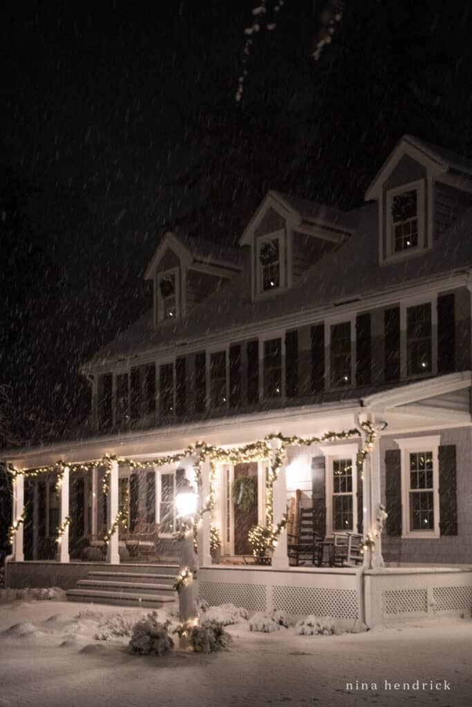 New England Colonial with Farmer's Porch and Christmas Lights on a snowy night