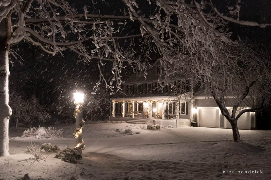 Snowy Christmas Colonial Home at Night with Lanterns and Christmas Lights