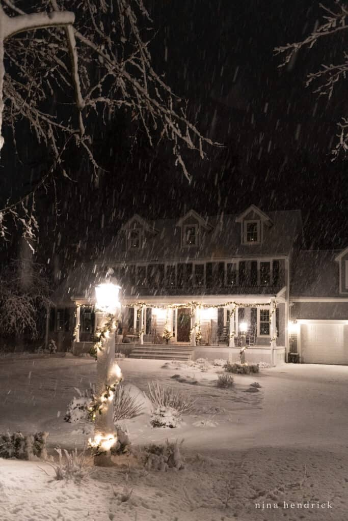 Christmas Home Tour at Night of a Snow New England Home with Lights and Garlands