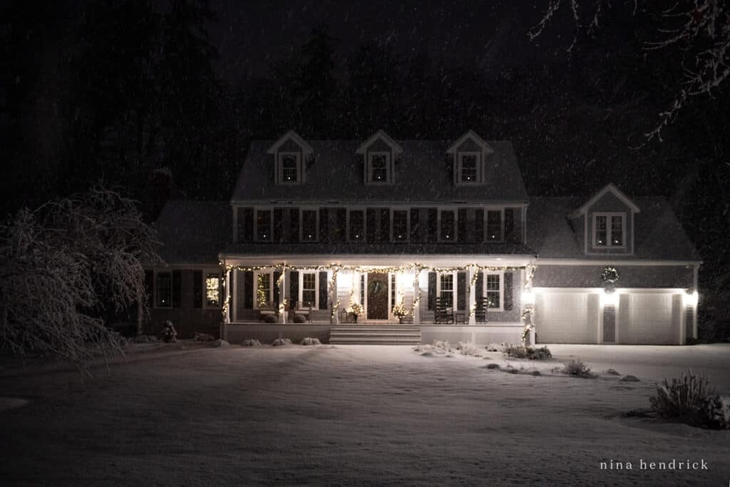 New England Colonial with Dormers and snow with Christmas Lights at Night