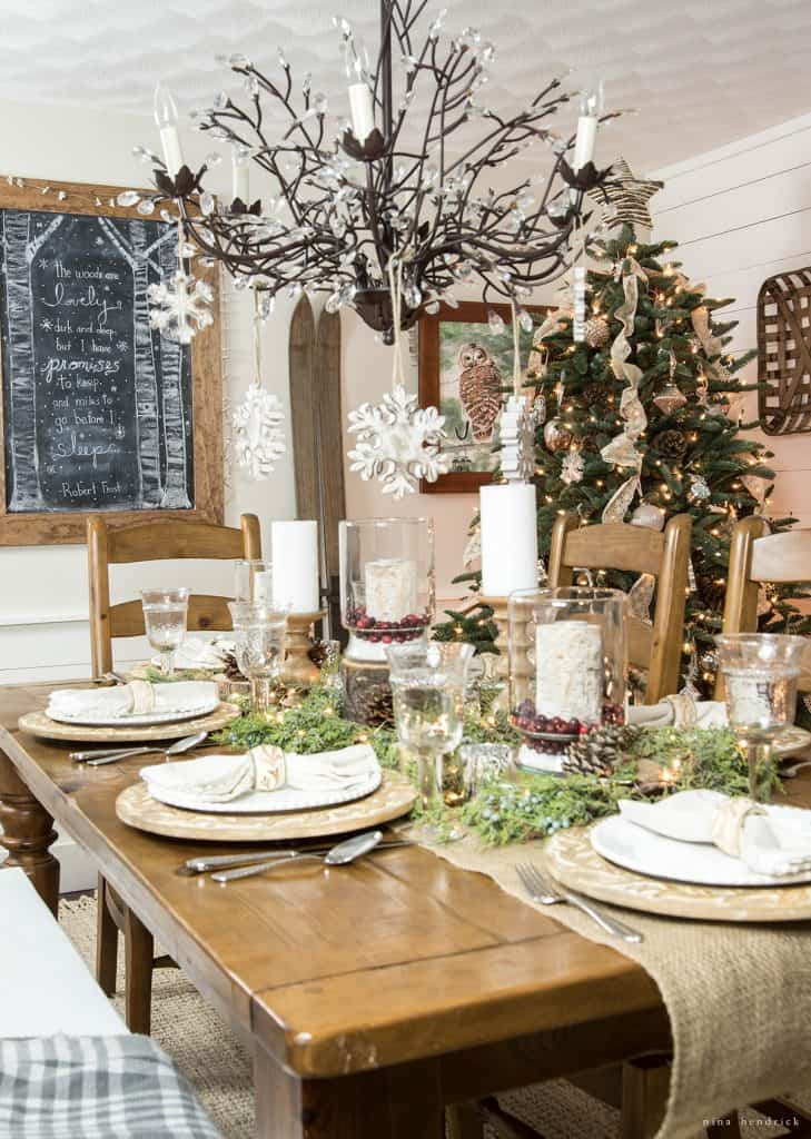 Christmas 2016 Nina Hendrick Holiday Housewalk | Gather inspiration from this tablescape with wood chargers, juniper greens, and hurricane luminaries.