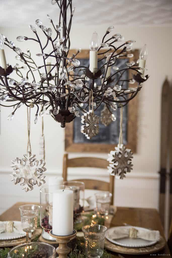 Christmas 2016 Nina Hendrick Holiday Housewalk | Hang white and wood ornaments on your chandelier to add interest to your holiday tablescape.