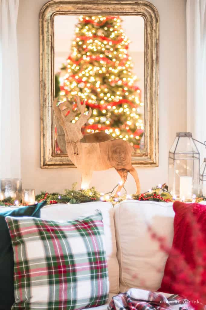 Wooden deer decor with Christmas tree lights in the mirror