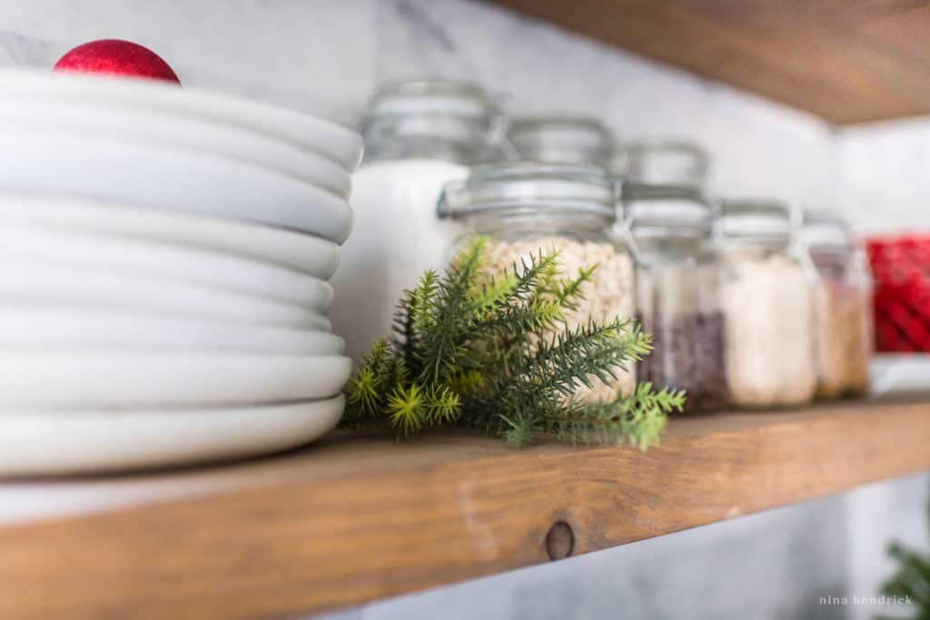 A sprig of greenery on a kitchen shelf decorated for Christmas.