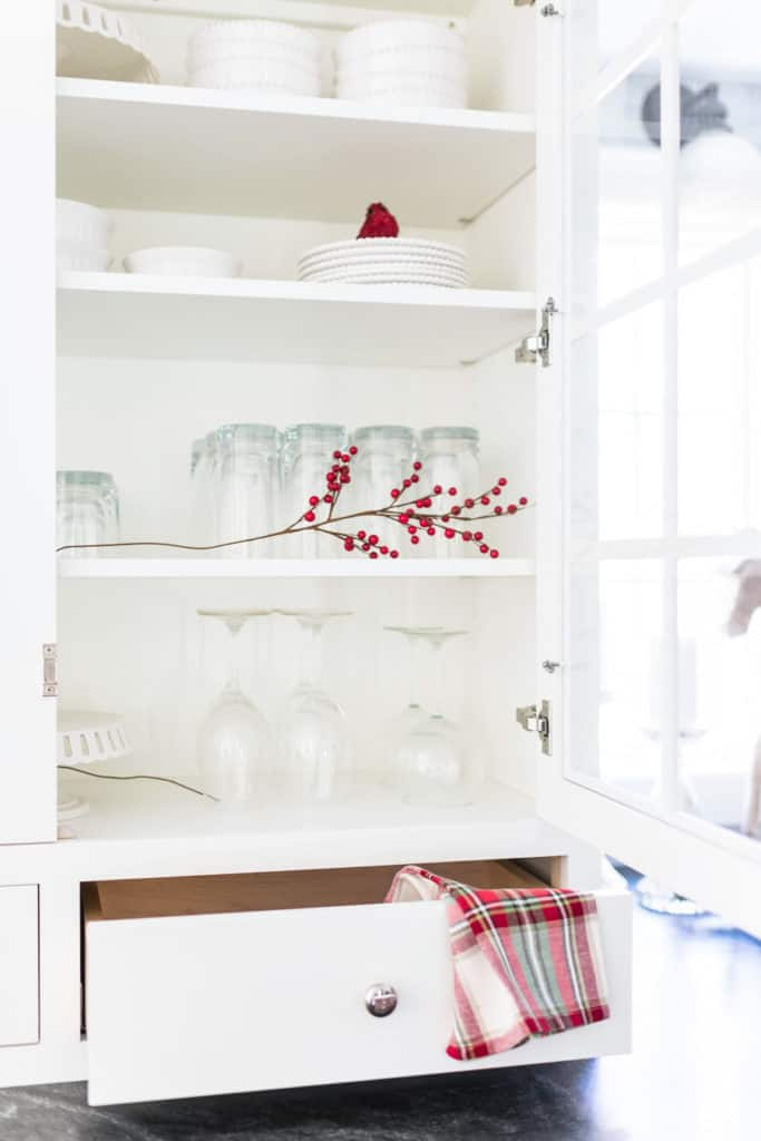 White Kitchen Hutch decorated for Christmas with a red and green plaid napkin.