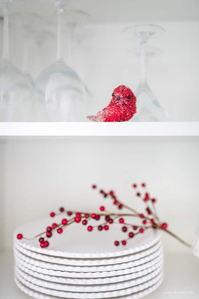 Christmas shelf vignette with small red bird and red berries.