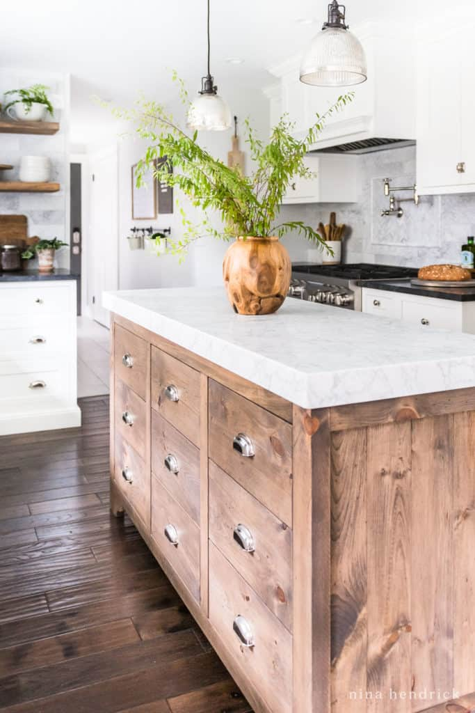 custom built white pine stained wood kitchen island with a marble top