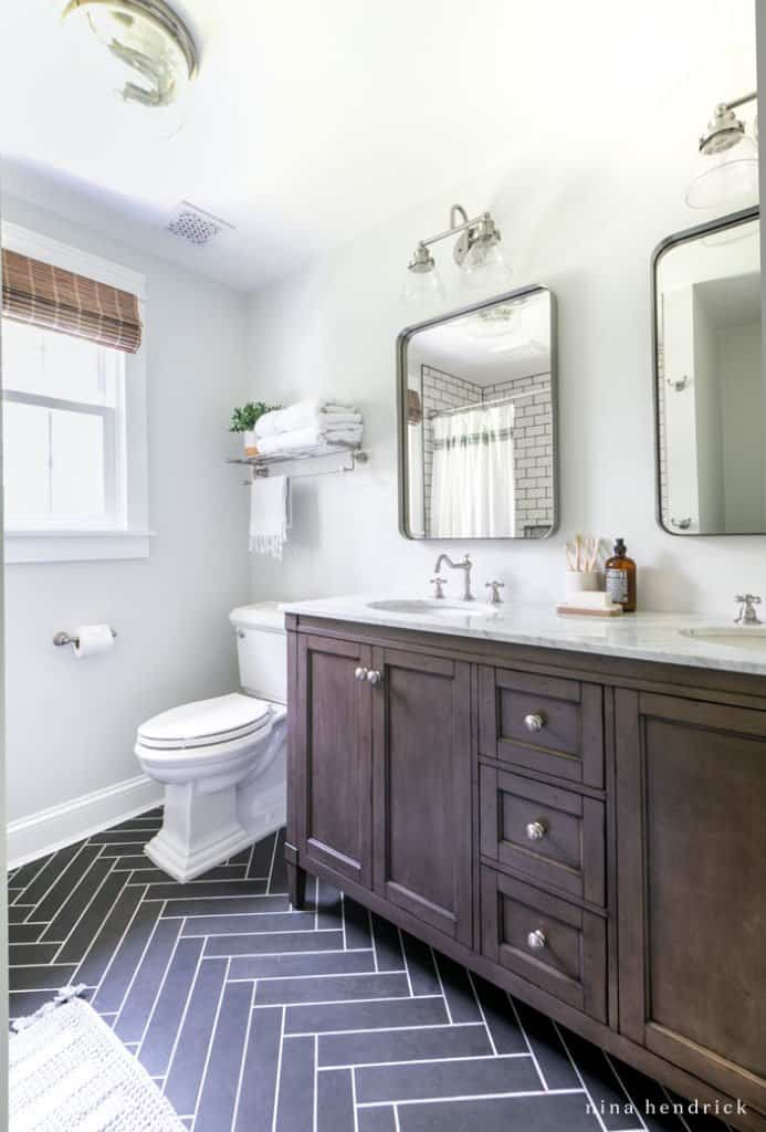 Small bathroom makeover with a dark wood vanity and herringbone tile floor.