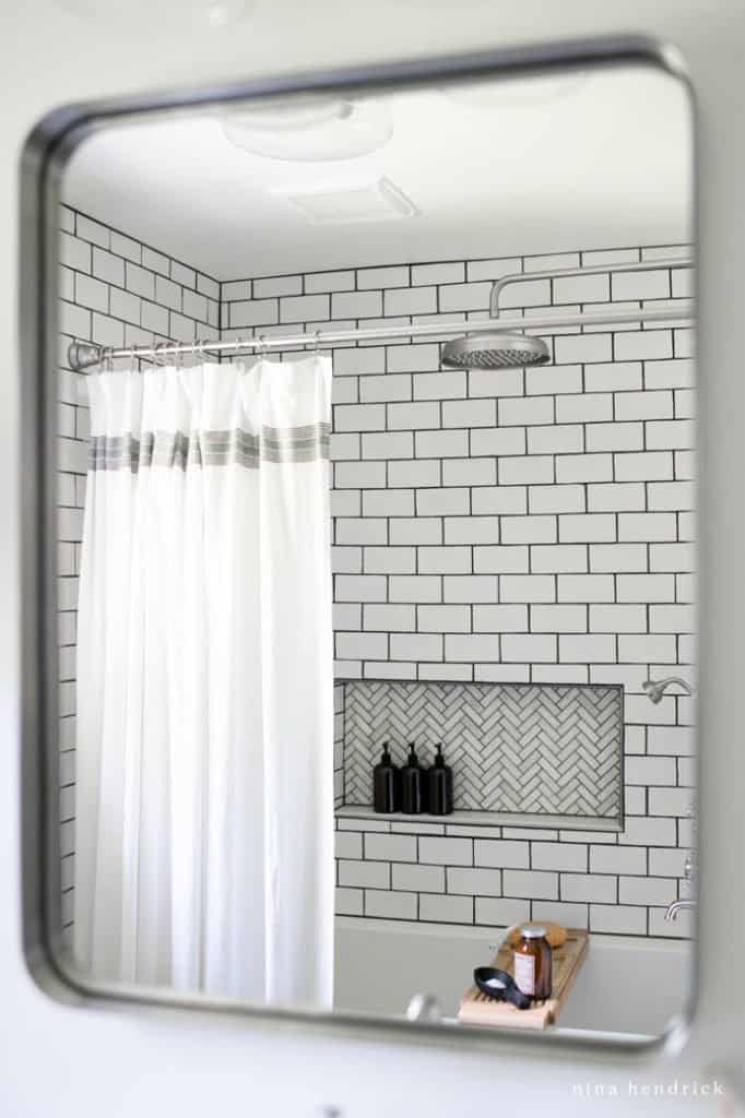 The view of a new shower in a small bathroom makeover from the mirror