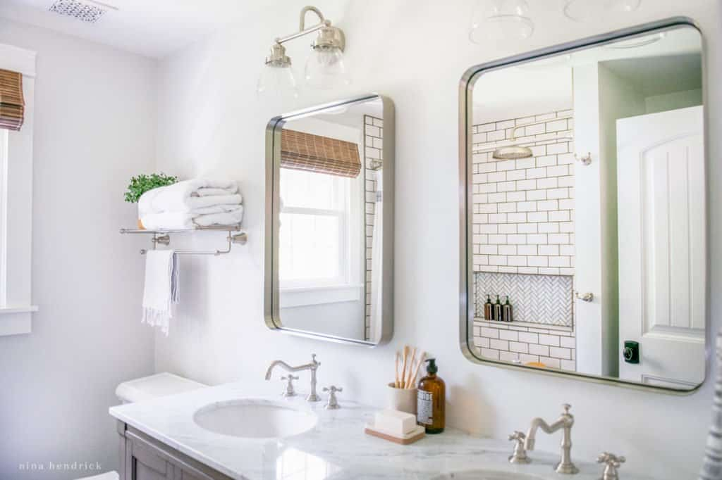 Rounded rectangle polished nickel mirrors add light to a small bathroom makeover.