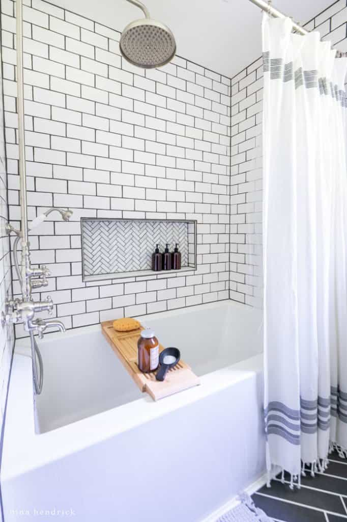 DIY replacement shower with a subway tile surround and herringbone marble niche in a small bathroom makeover.