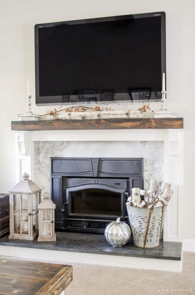 Formerly brick fireplace covered with wood and stone with a rustic mantel.