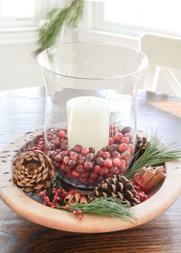 Cozy Christmas decorating ideas including this glass hurricane with cranberries in a wooden bowl surrounded by pine needles, pinecones, and cinnamon.