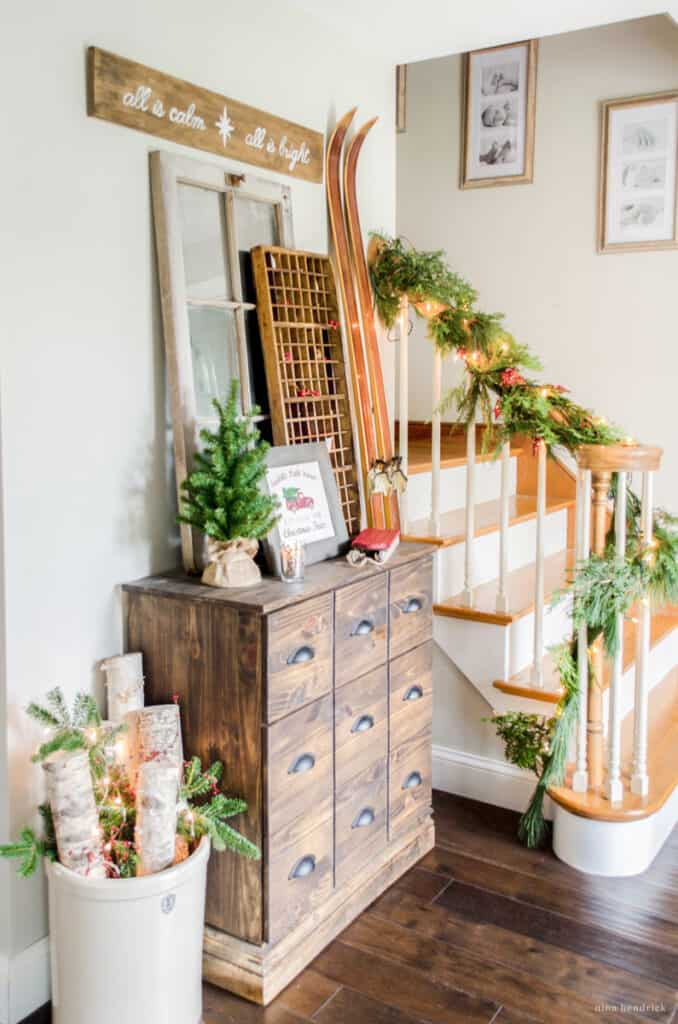 Warm and cozy Christmas decorating ideas for the foyer — vignette with card catalog and birch log arrangement with vintage skis.