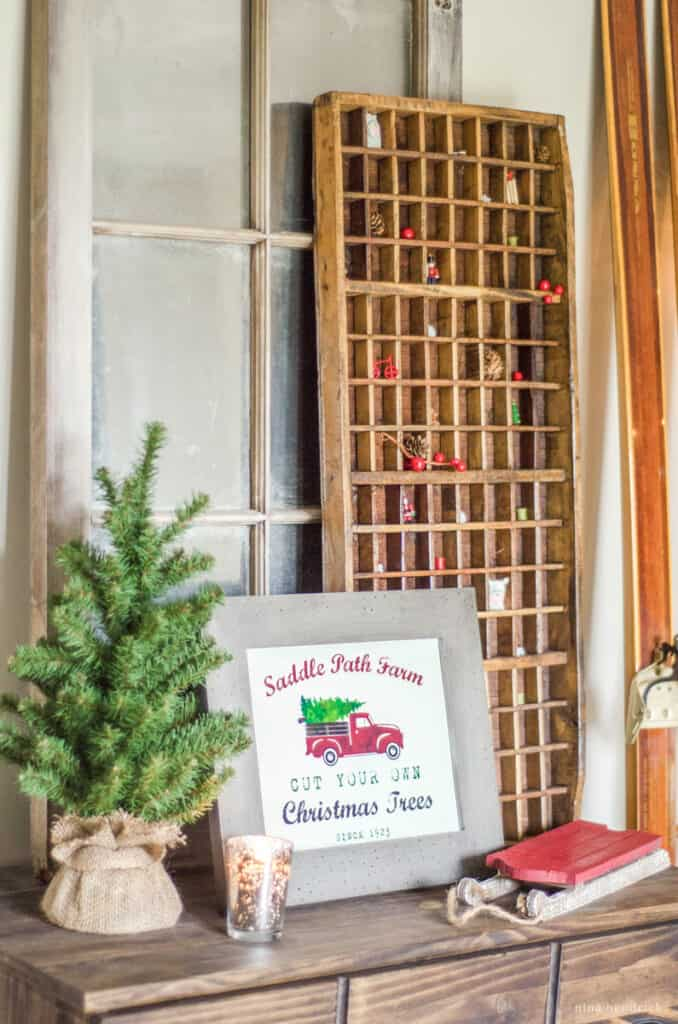Cozy Christmas vignette with miniature decor in a printer's tray and a red truck tree farm sign.