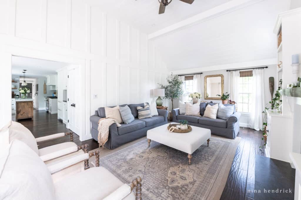 White family room with board-and-batten and tongue-and-groove with charcoal sofas.
