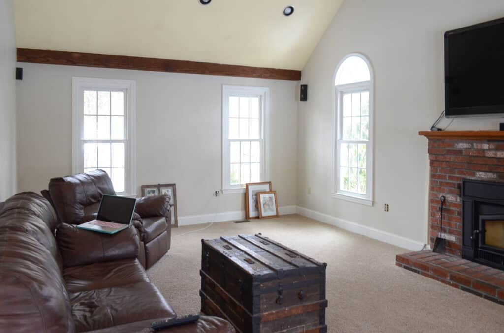 Family room before completing a renovation project with brown leather sofas and yellow ceilings.