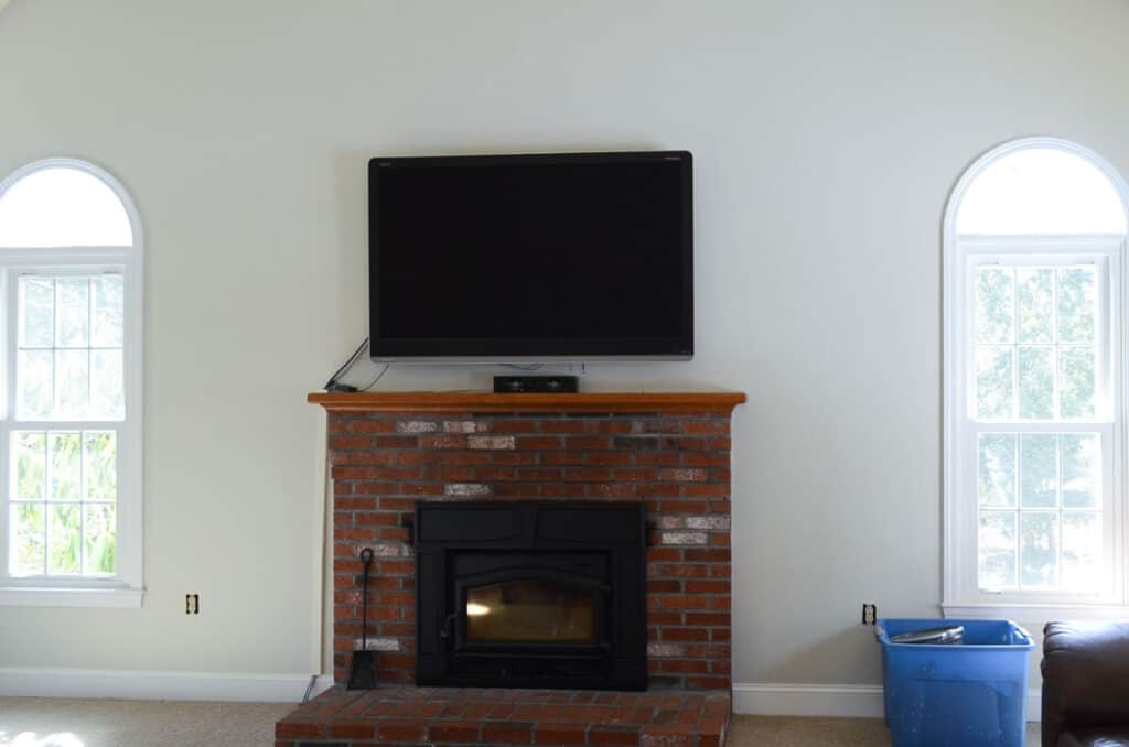 Family room painted Benjamin Moore Edgecomb Gray with brick fireplace and large TV