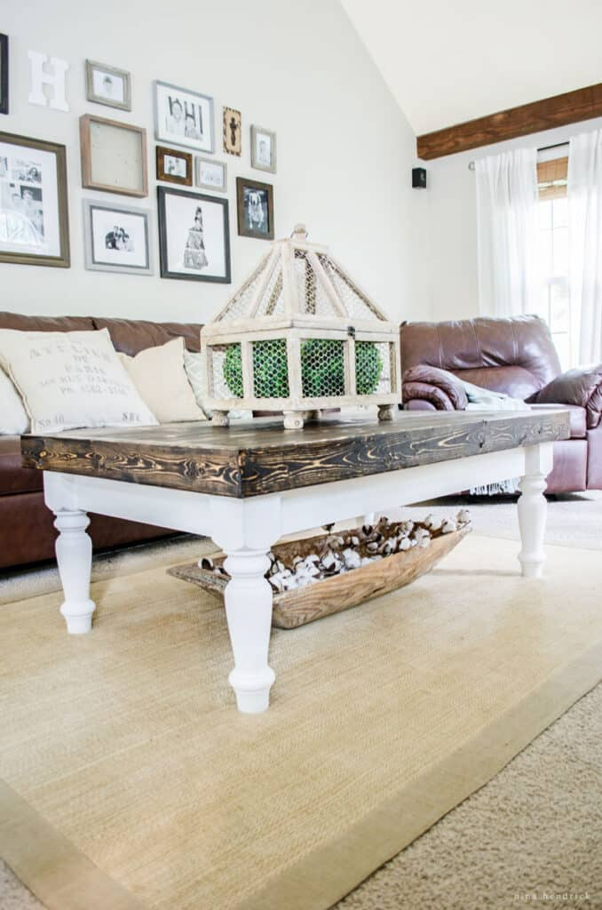 DIY wood cottage coffee table with a brown top and white legs in a living room with brown sofas.