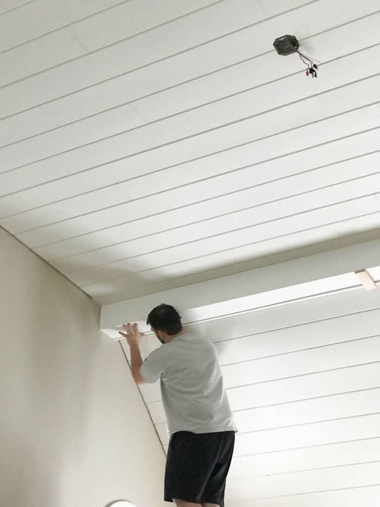 Covering a cathedral ceiling with white painted tongue-and-groove boards.