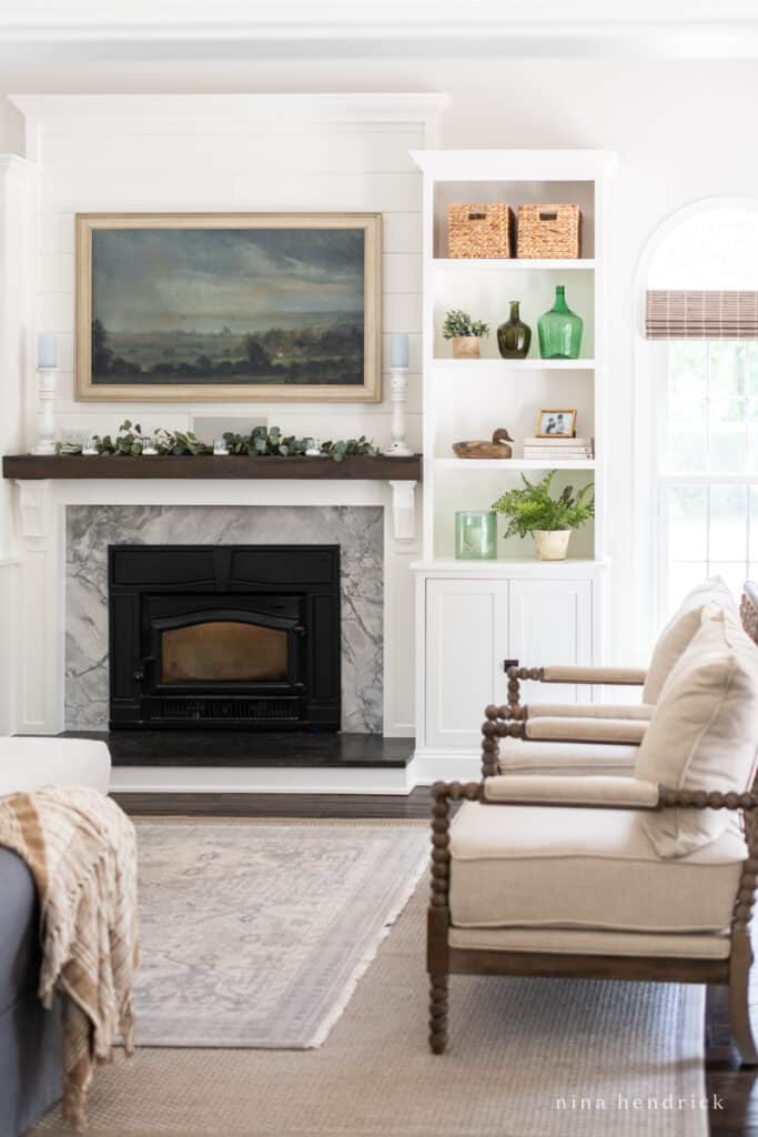 Family Room completed project with white fireplace built-ins styled with greenery and other decor.