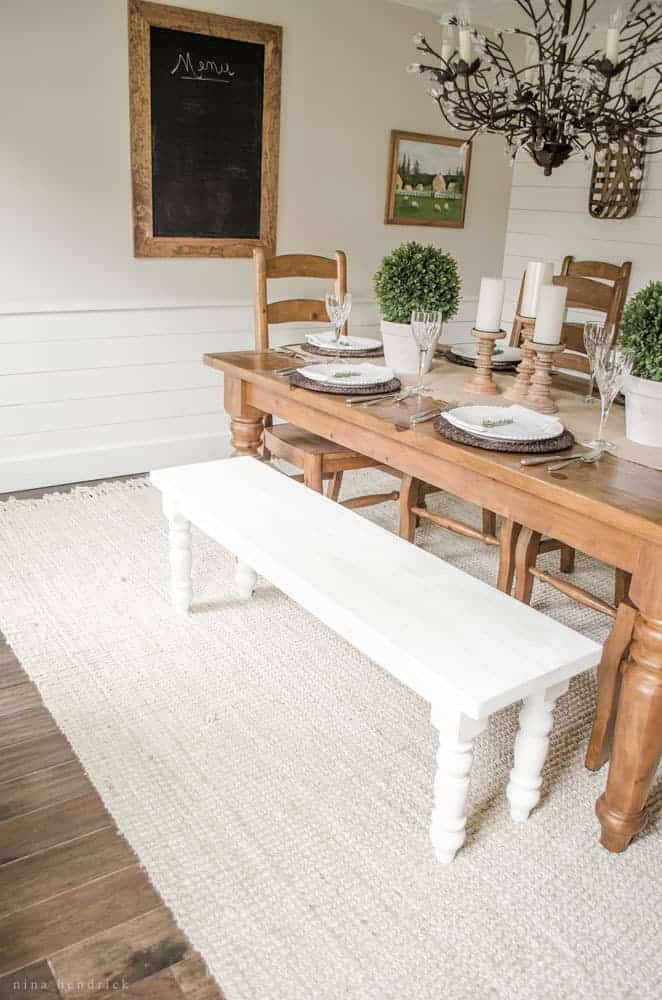 Rustic dining room with a wood farmhouse table and white bench