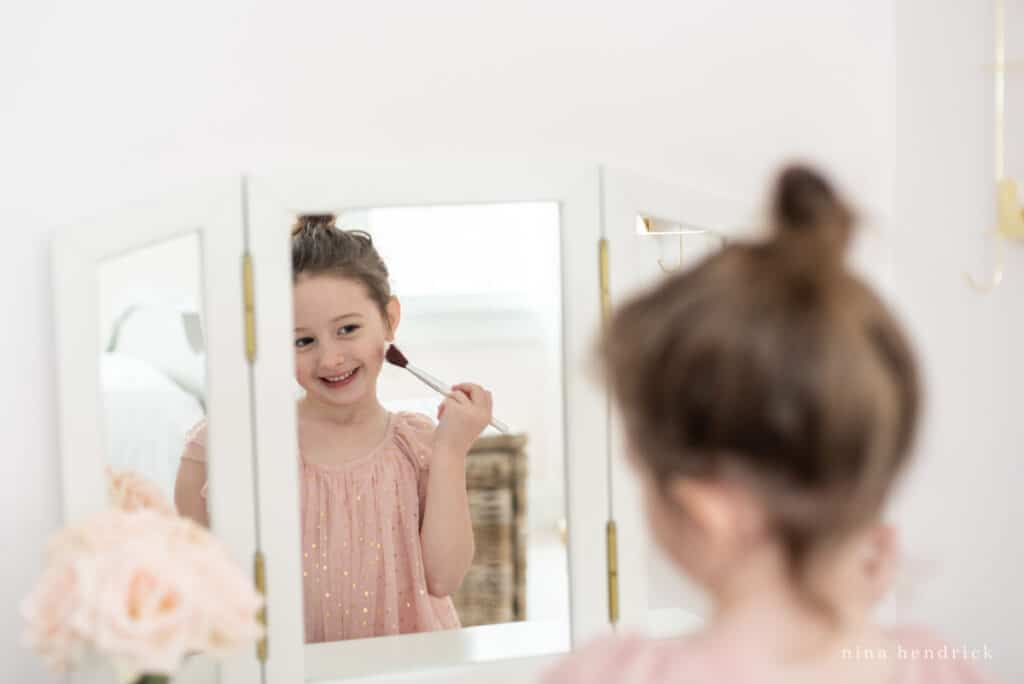 Little girl looking in vanity mirror