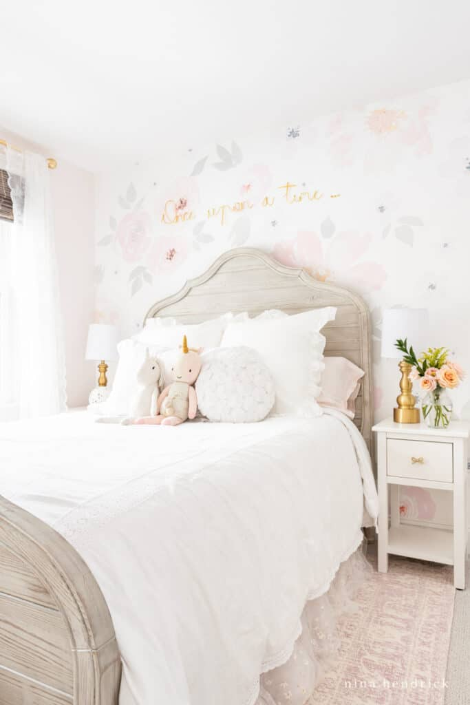Floral girl's bedroom makeover with unicorn stuffed animals and graywash bed.