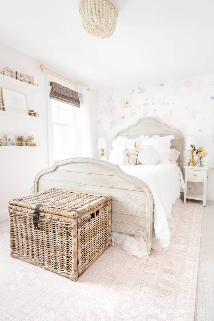Girl's floral bedroom makeover with vintage-inspired rug and wicker chest