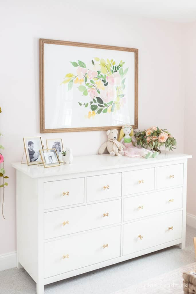 Fairy Tale Blush Floral Girl's Bedroom Makeover gold bows on dresser and gold frames.