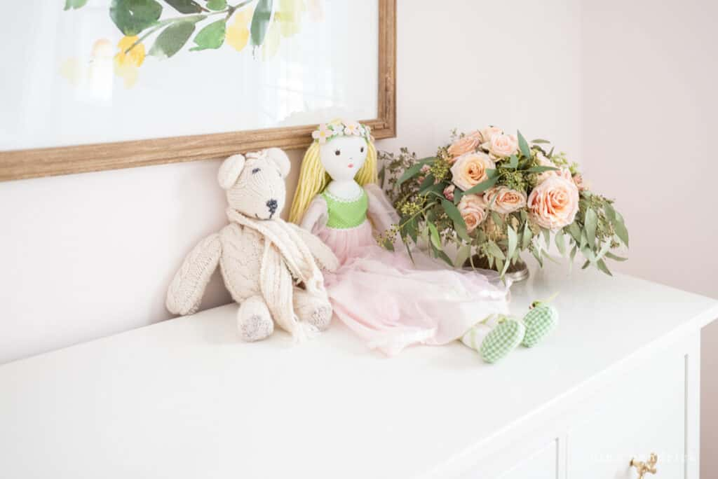Doll and teddy bear with flowers on a dresser.