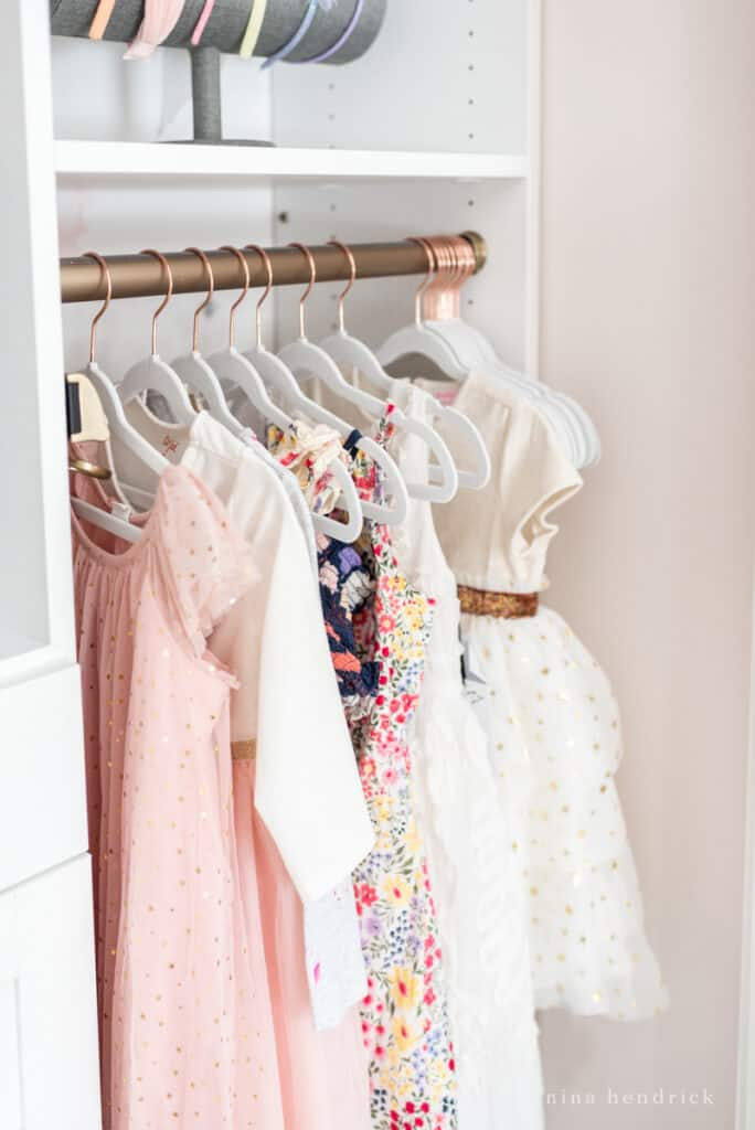girl's organized closet makeover with velvet hangers and pretty princess dresses