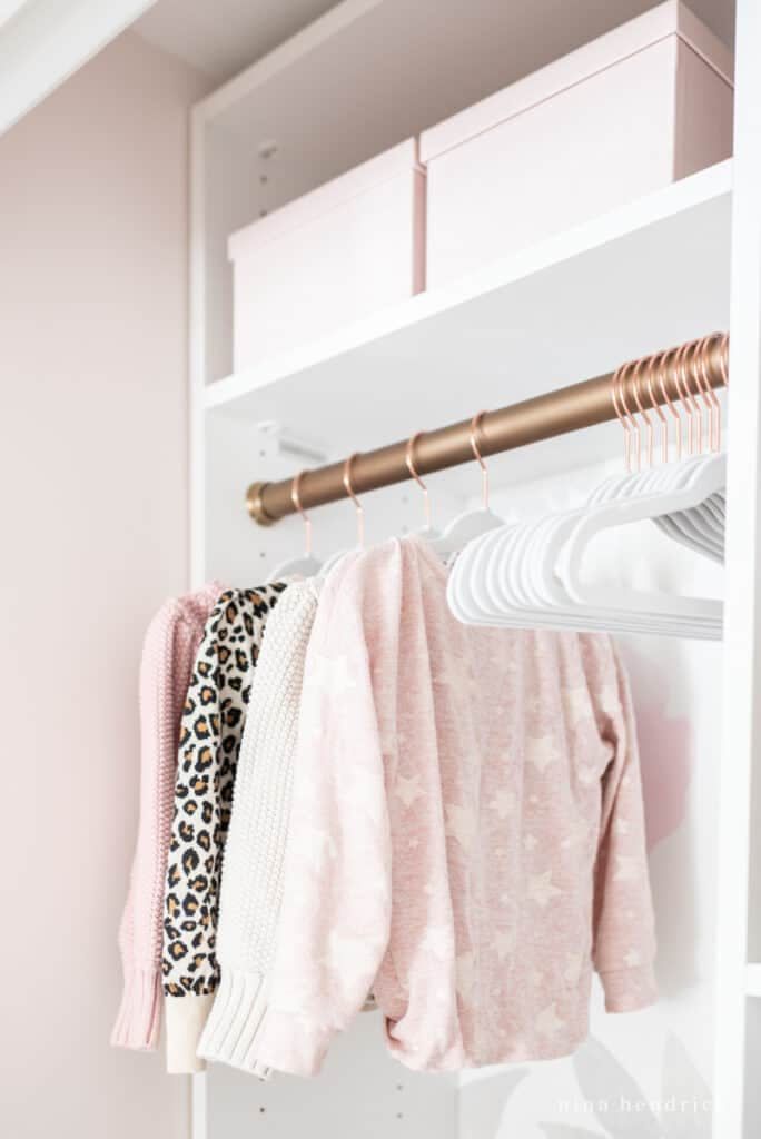 Girl's organized sweaters with gold closet rod and velvet hangers
