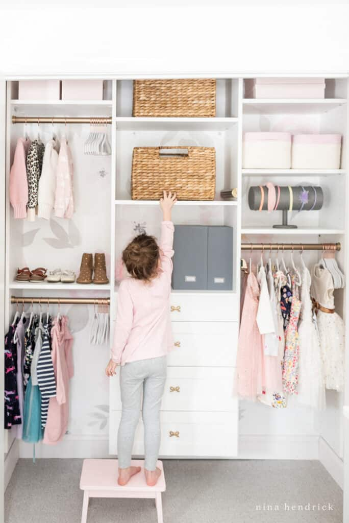 organized little girl's closet makeover with floral wallpaper
