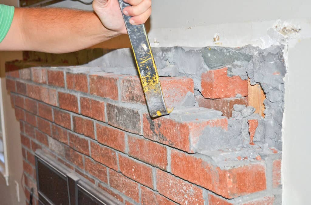 Demoing a brick fireplace and removing the top courses to wrap it in wood.