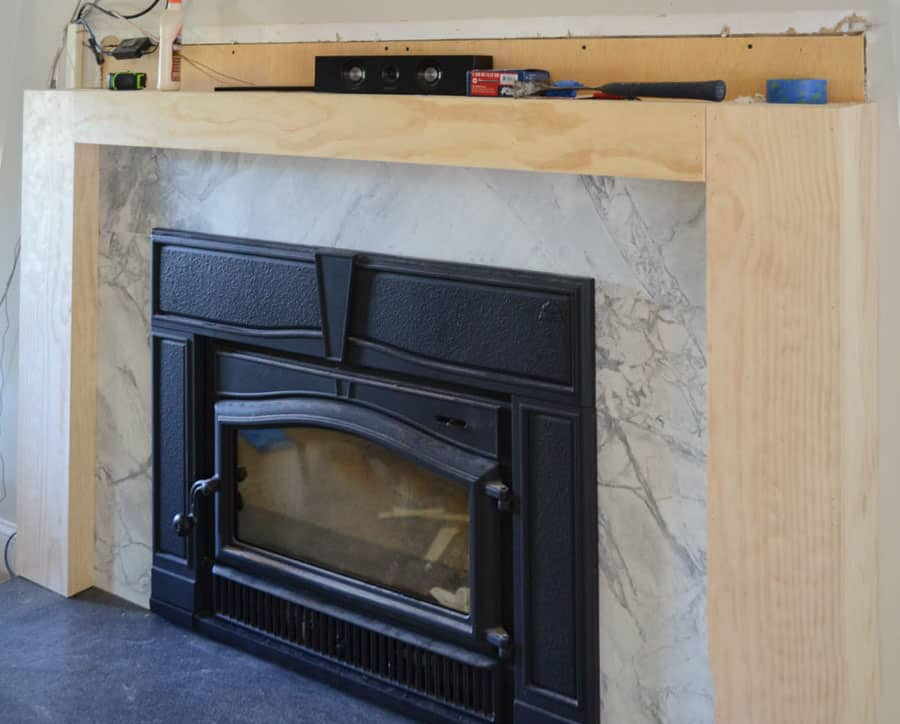 Brick fireplace covered with wood surround awaiting trim