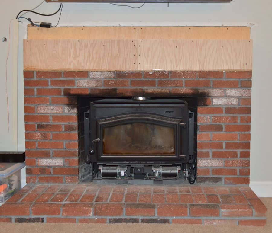 brick fireplace with wood building out the top courses in anticipation of stone.