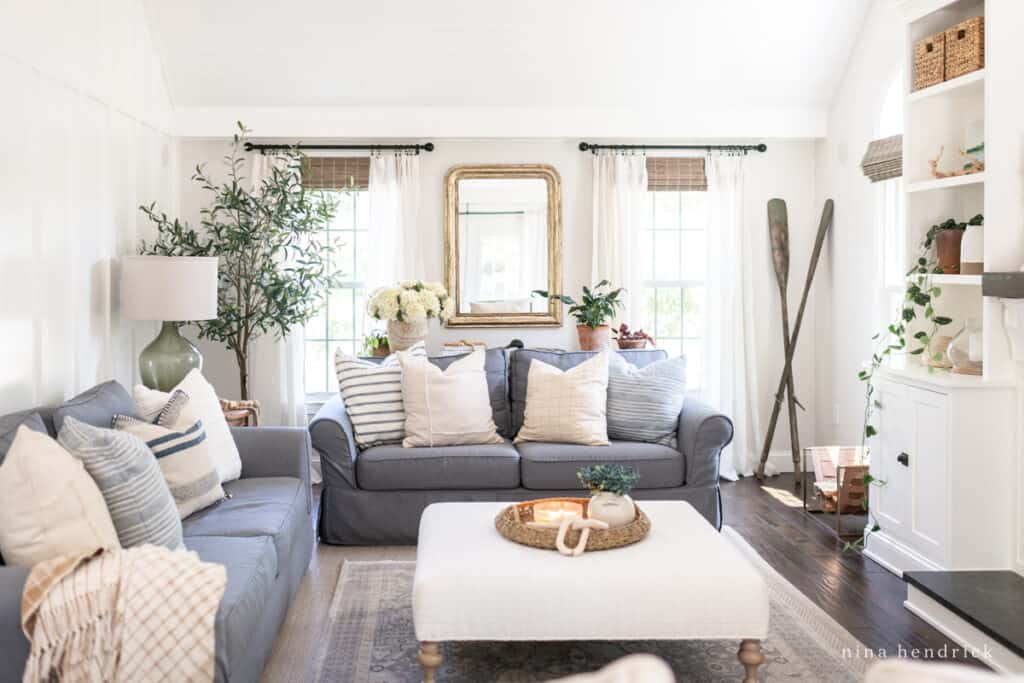 Family room decorated with natural and neutral style with white walls and a charcoal sofa.