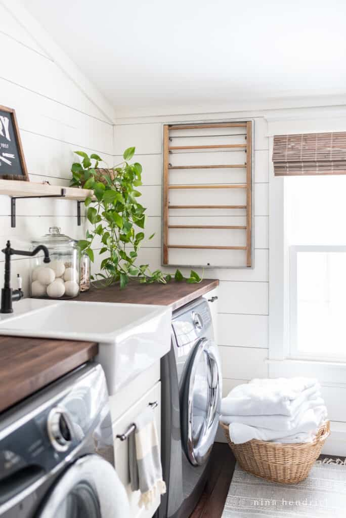 Laundry room makeover with a dark countertop and white planked walls