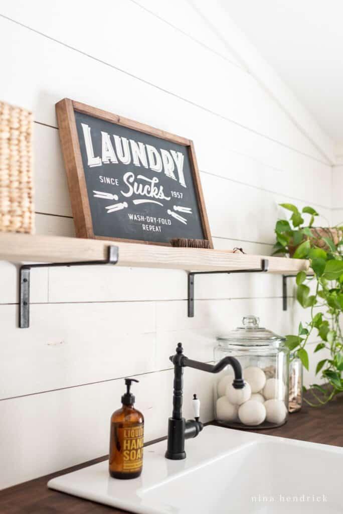 laundry sucks sign over a white farmhouse sink