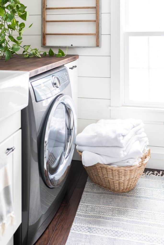 basket with freshly folded towels in front of the washer machine