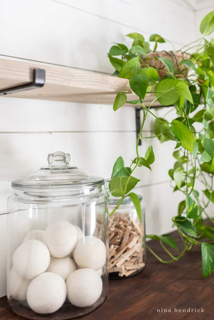glass jars with laundry supplies like wool dryer balls and clothespins plus a trailing houseplant